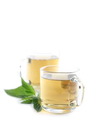 Nettle and freshly made nettle tea in glass cups isolated on white background  Shallow dof Stock Photo - 14782110