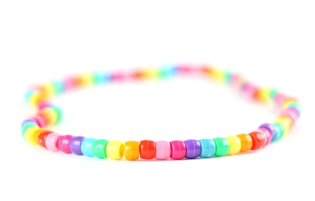Close-up of a colorful bead necklace isolated on white background  Shallow dof photo