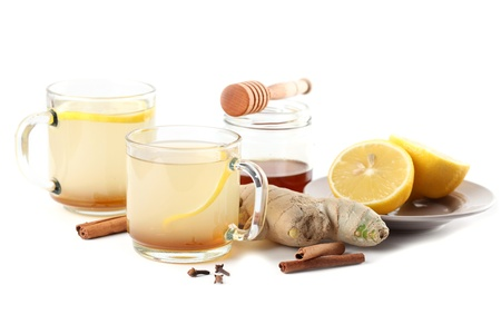 Ginger tea with honey, lemon, cinnamon and cloves isolated on white background photo