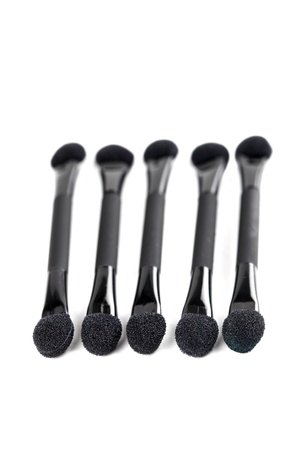 Close-up of five black make-up applicators isolated on white background photo