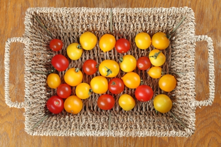 directly above: Yellow and red cherry tomatoes in a basket  Shallow dof Stock Photo