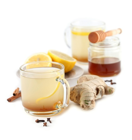 Ginger tea with honey lemon cinnamon and cloves isolated on white background photo