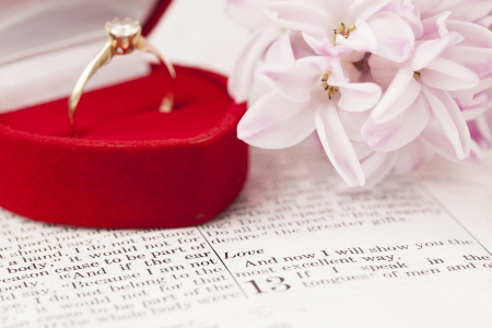 Gold engagement ring with diamond on the Bible open to 1st Corinthians 13, a passage about love  Shallow dof photo