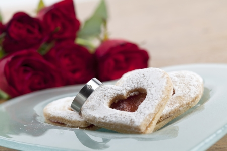 Titanium engagement ring with shortbread hearts on a plate and red roses  Shallow dof photo