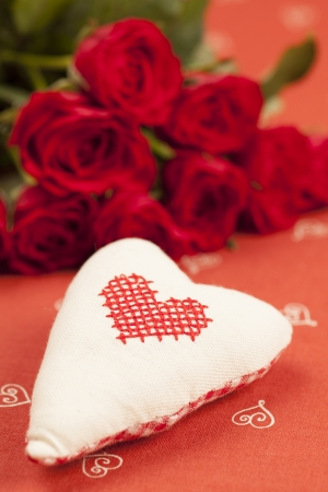 Embroidered fabric heart and red roses on red background  Shallow dof photo