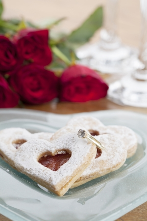 Gold engagement ring with shortbread hearts on a plate, red roses and wine glasses  Shallow dof photo