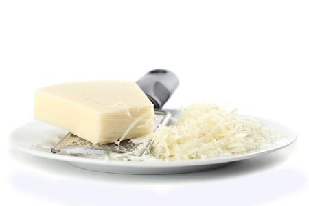 queso rallado: Queso rallado y rallador en un plato aislado en fondo blanco