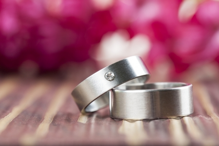 Titanium wedding rings with red hyacinth in the background  Shallow dof Stock Photo