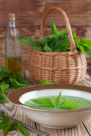 Nettle cream soup on wooden background  Shallow dof Stock Photo