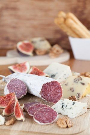 tabla de quesos: Carne con queso, higos, nueces y grisines Foto de archivo