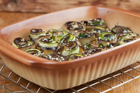 hemp hemp seed: Eggplant and zucchini rolls on baking sheet with hemp seed
