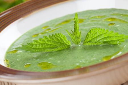 nettle: Nettle cream soup on wooden background  Shallow dof Stock Photo