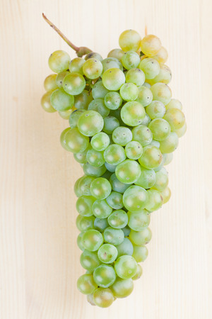 grape cluster: Green grape cluster on wooden background. Shallow dof Stock Photo
