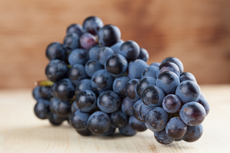 grape cluster: Blue grape cluster on wooden background. Shallow dof