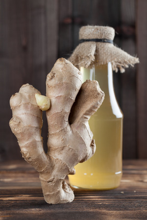 jarabe: raíz de jengibre y una botella con jarabe de jengibre. Kelvin superficial Foto de archivo