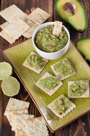 tex mex: Bowl with freshly made guacamole and crackers. Shallow dof