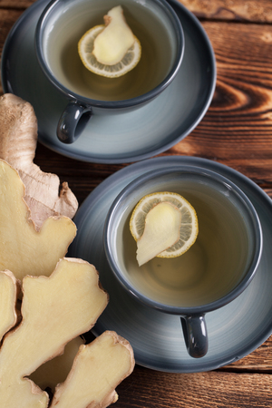 ginger tea: Two cups of ginger tea with a slice of ginger and lemon. Shallow dof