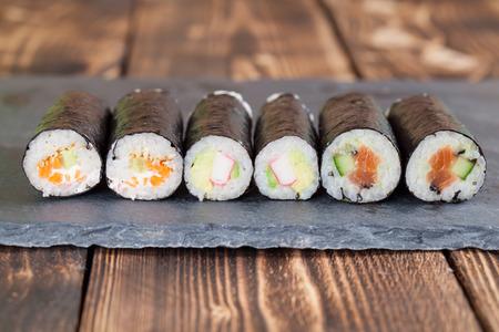 algas marinas: Caseras rollos de maki sushi en una placa de pizarra Foto de archivo