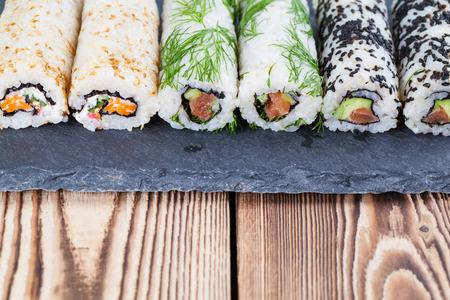 slate board: Homemade uramaki sushi rolls on a slate board