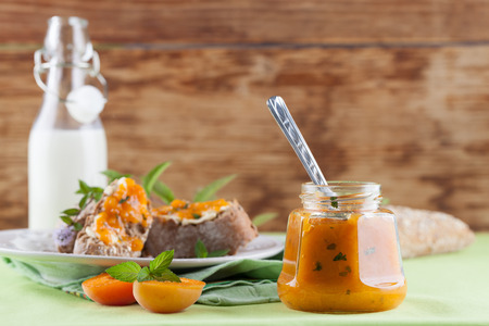 apricot jam: Jar with spicy apricot jam with mint. Bread and milk in the background
