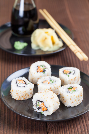 Uramaki sushi with carrot, cucumber, surimi and roasted white sesame. Shallow dof Stock Photo
