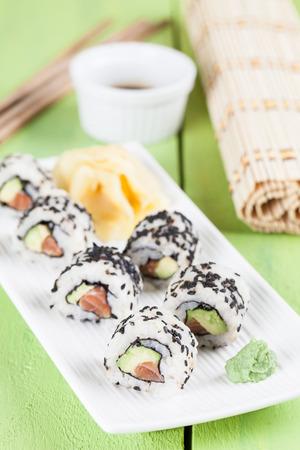 black sesame: Uramaki sushi with avocado, raw salmon and black sesame. Shallow dof