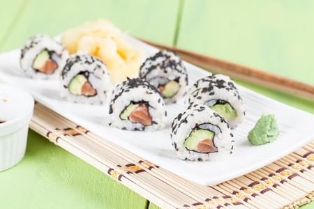 Uramaki sushi with avocado, raw salmon and black sesame. Shallow dof