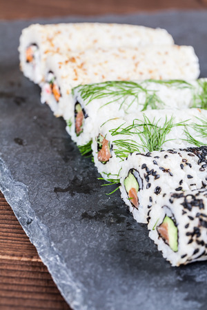 Homemade uramaki sushi rolls on a slate board