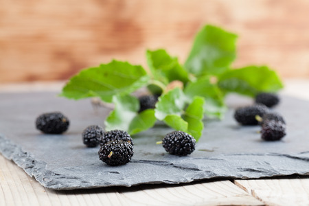 Black mulberries spilt on a slate board. Shallow dof
