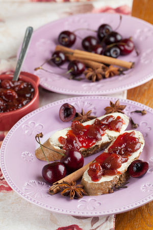 Bread with homemade spicy cherry jam. Shallow dof Stock Photo