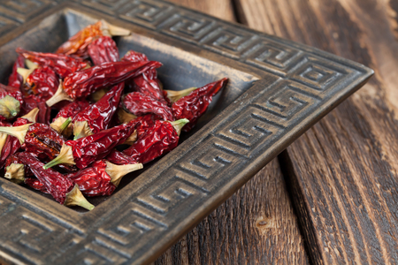 Dried red chili peppers in a bowl. Shallow dof Stock Photo