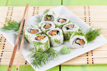 Uramaki sushi with cucumber, raw salmon and dill. Shallow dof