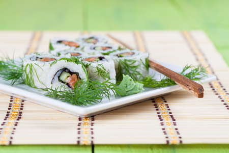 Uramaki sushi with cucumber, raw salmon and dill. Shallow dof