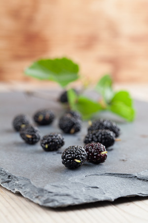 black boards: Black mulberries spilt on a slate board. Shallow dof