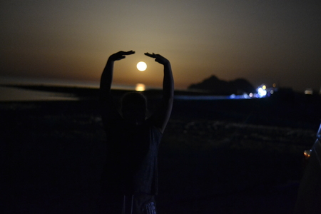 Silhouette of a woman doing yoga by the moonlight in the beach