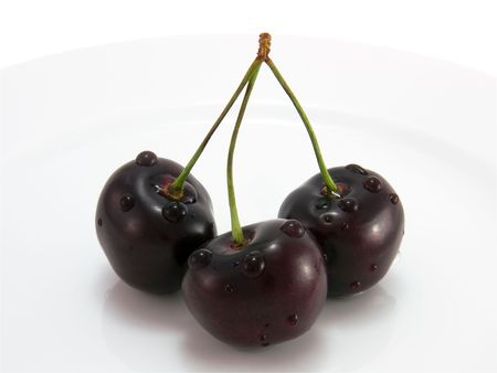 Black cherry on a plate on a white close-up Standard-Bild