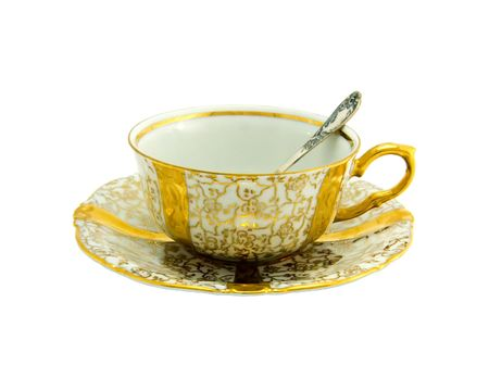 Gold porcelain cup with a saucer and silver spoon from a tea-set