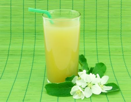 Glass of fresh apple juice and white flowers