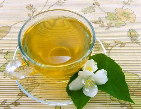 Transparent teacup with tea and flower of jasmin