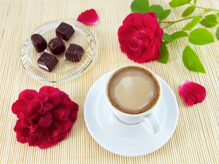 Cup of coffee with cream, chocolate candies and red rose Stock Photo