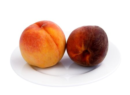 Ripe peaches in a porcelain plate on a white
