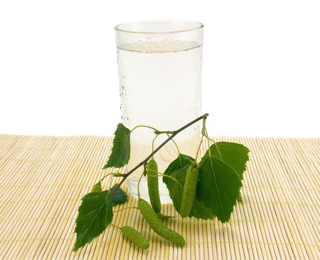 Glass of birch juice, water drops and birch branch, close-up Standard-Bild