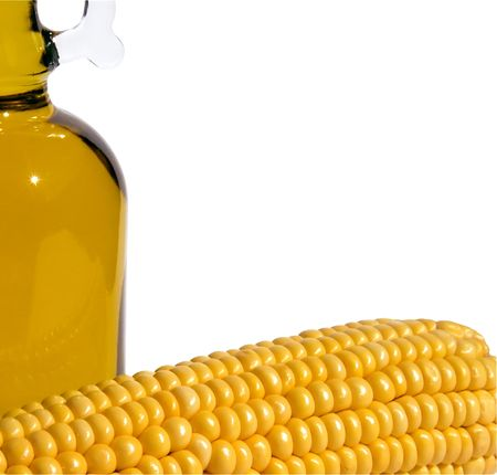 Corn and bottle of oil on a white close-up