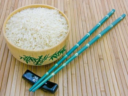 Wooden bowl with rice, chopsticks on bamboo mat close-up