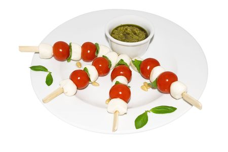 Mozzarella, cherry tomatoes, pesto and basil on a white background Stock Photo