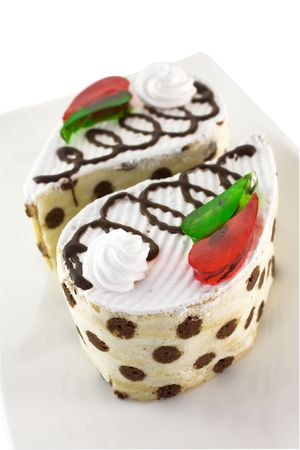 Cake vanilla-chocolate sponge with whipped cream and pieces of colored jelly