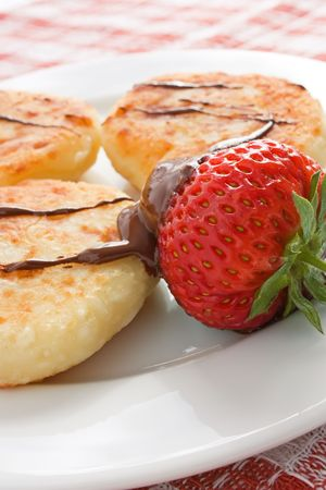 Cheese pancakes with chocolate syrup and strawberry