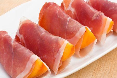 Slices of peach in Prosciutto Italian cured ham