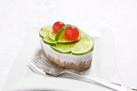 Sponge cake with whipped cream and slices of lime and cherry