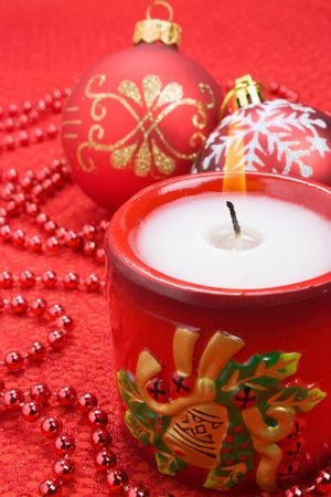 Christmas candle and red balls decorations close-up